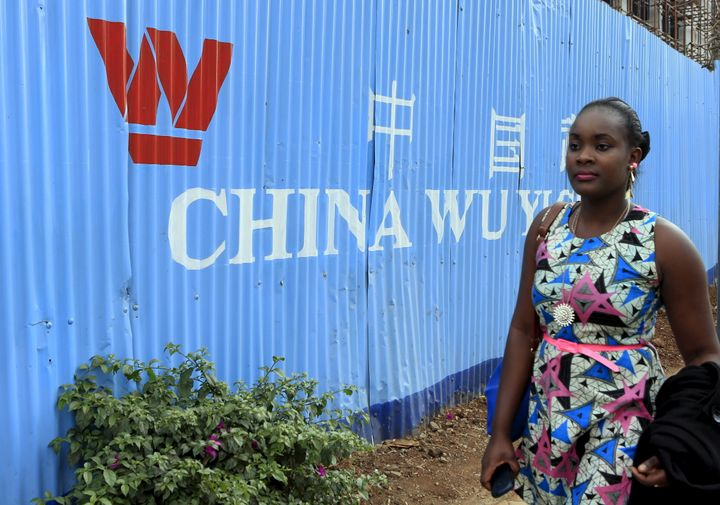 A woman walks past corrugated iron fencing at a Chinese construction site in Kenya's capital Nairobi on September 2, 2015.