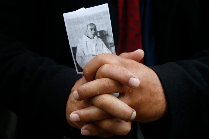 A mourner holds a picture of slain French parish priest Father Jacques Hamel during a funeral ceremony at the Cathedral in Ro