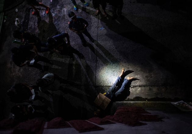 Police look atthe dead body of an alleged drug dealer, his face covered with packing tape and a...