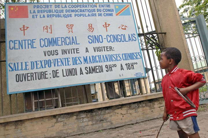 A Congolese boy looks up towards a sign advertising a commercial center selling Chinese products on November 3, 2006 in Kinsh