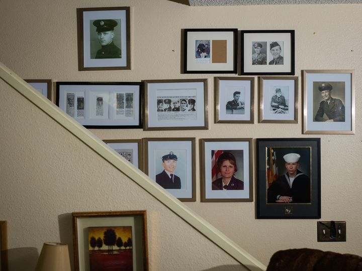 Tina Cramer Showers comes from a family of veterans. A wall in her home in Anchorage, Alaska, displays some of their photos.