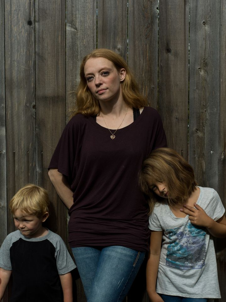 Army veteran Micki Millecam, 31, stands with her two children, Tucker, 4, and Mariah, 7, outside of their home in Soldotna, A