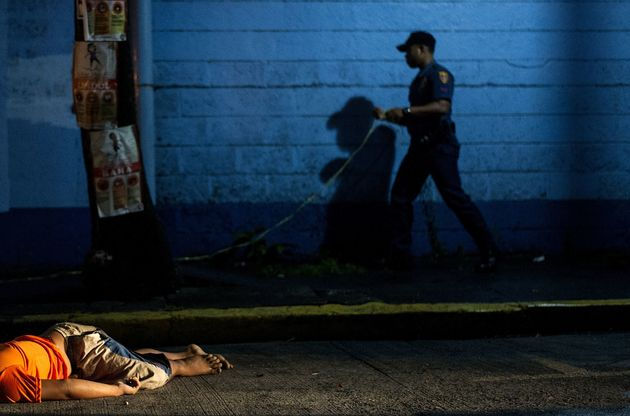 The body of a man, shot dead by unidentified gunmen, lies on the ground in Manila on July 23,