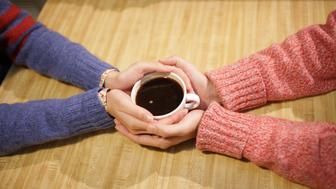 Couple holding a cup of coffee