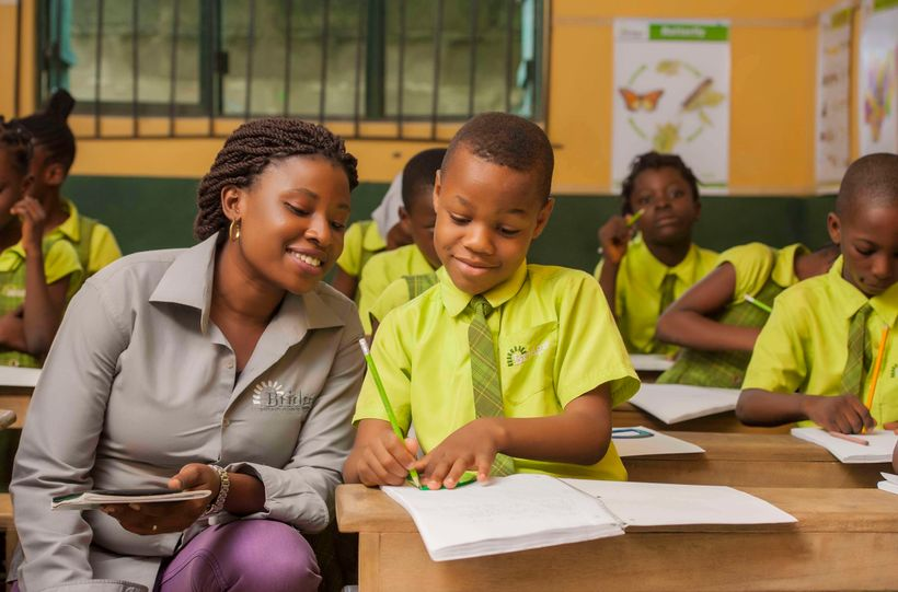 A teacher at Bridge International Academies in Nigeria guides a pupil during independent study