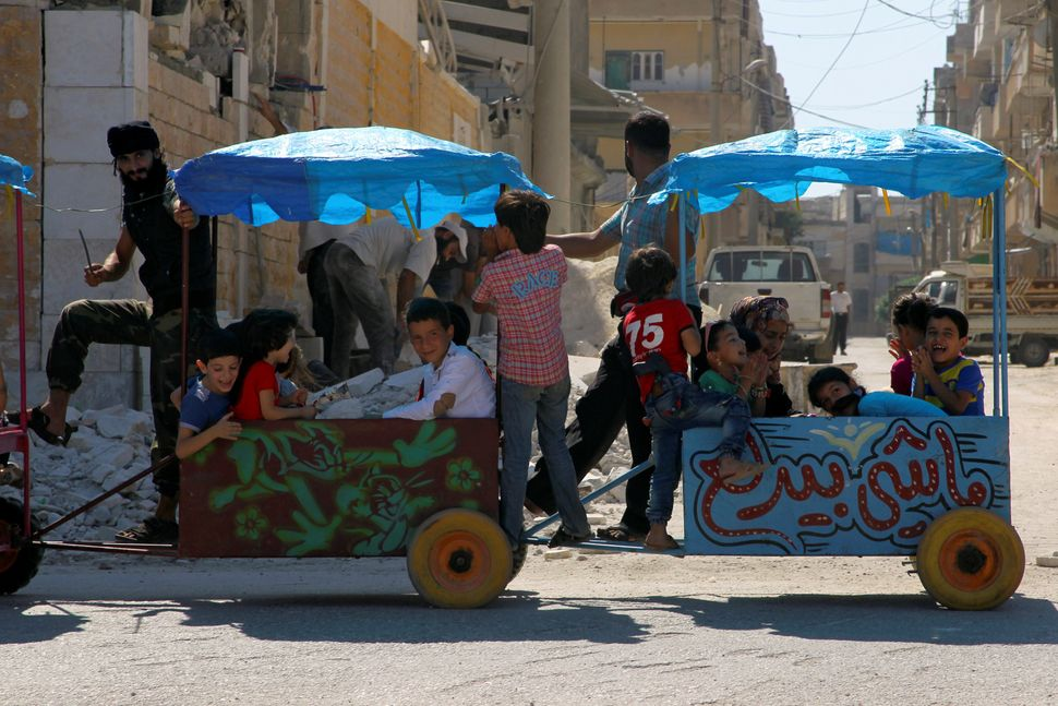 Children ride a cart in the rebel controlled city of Idlib.
