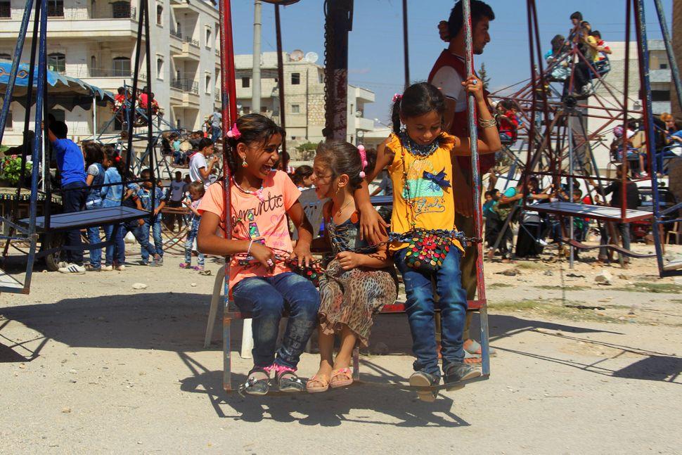 Children play on swings inIdlib.