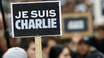People hold a poster reading 'Je suis Charlie (I am Charlie)' during a Unity rally Marche Republicaine in Paris on January 11, 2015 in tribute to the 17 victims of a three-day killing spree by homegrown Islamists. The killings began on January 7 with an assault on the Charlie Hebdo satirical magazine in Paris that saw two brothers massacre 12 people including some of the country's best-known cartoonists, the killing of a policewoman and the storming of a Jewish supermarket on the eastern fringes of the capital which killed 4 local residents.    AFP PHOTO / PATRICK KOVARIK        (Photo credit should read PATRICK KOVARIK/AFP/Getty Images)