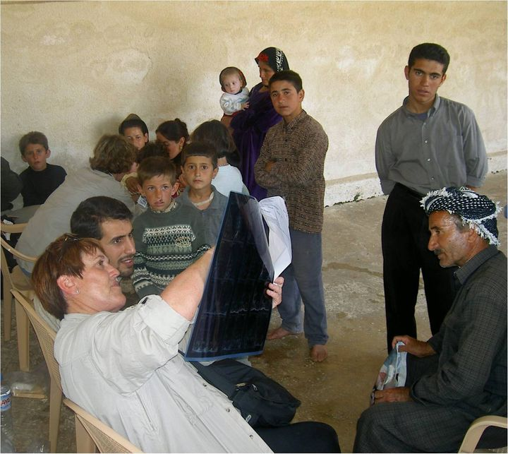 Mary Burry surrounded by local villagers, reviews a patient X-Ray inside the Iraqi village's mosque.