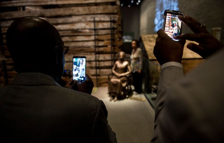A woman poses with a sculpture of the freed slave Clara Brown.