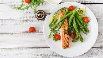 Baked salmon garnished with asparagus and tomatoes with herbs. Top view