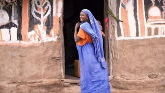A Oromo woman the largest ethnic group of Ethiopia stands in front of her home