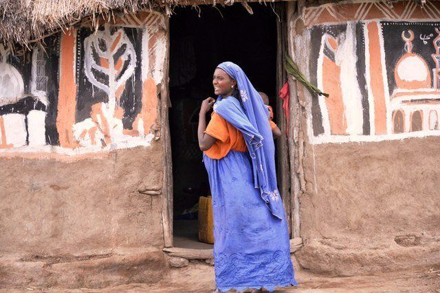 A Oromo woman, the largest ethnic group of Ethiopia, stands in front of her home.