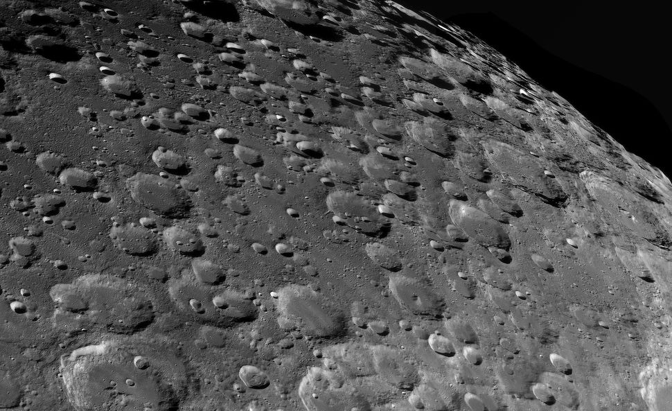 A close-up view of the lunar landscape littered with craters and craterlets largely forged by the impact of meteors and
