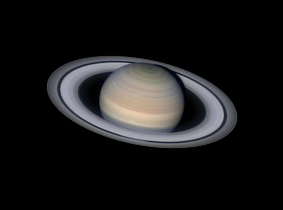 Saturn, the second largest planet in our solar system, appears with its famed rings. Storms are visible across the