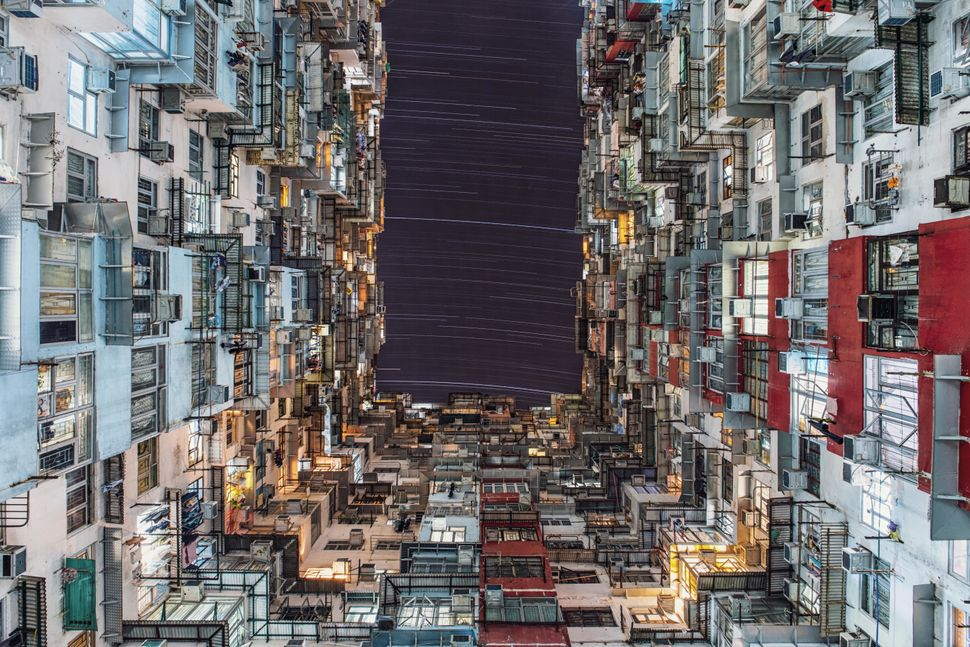 Star trails highlighting the movement of the Earth gently arc over the towering buildings in the bustling Quarry Bay nei