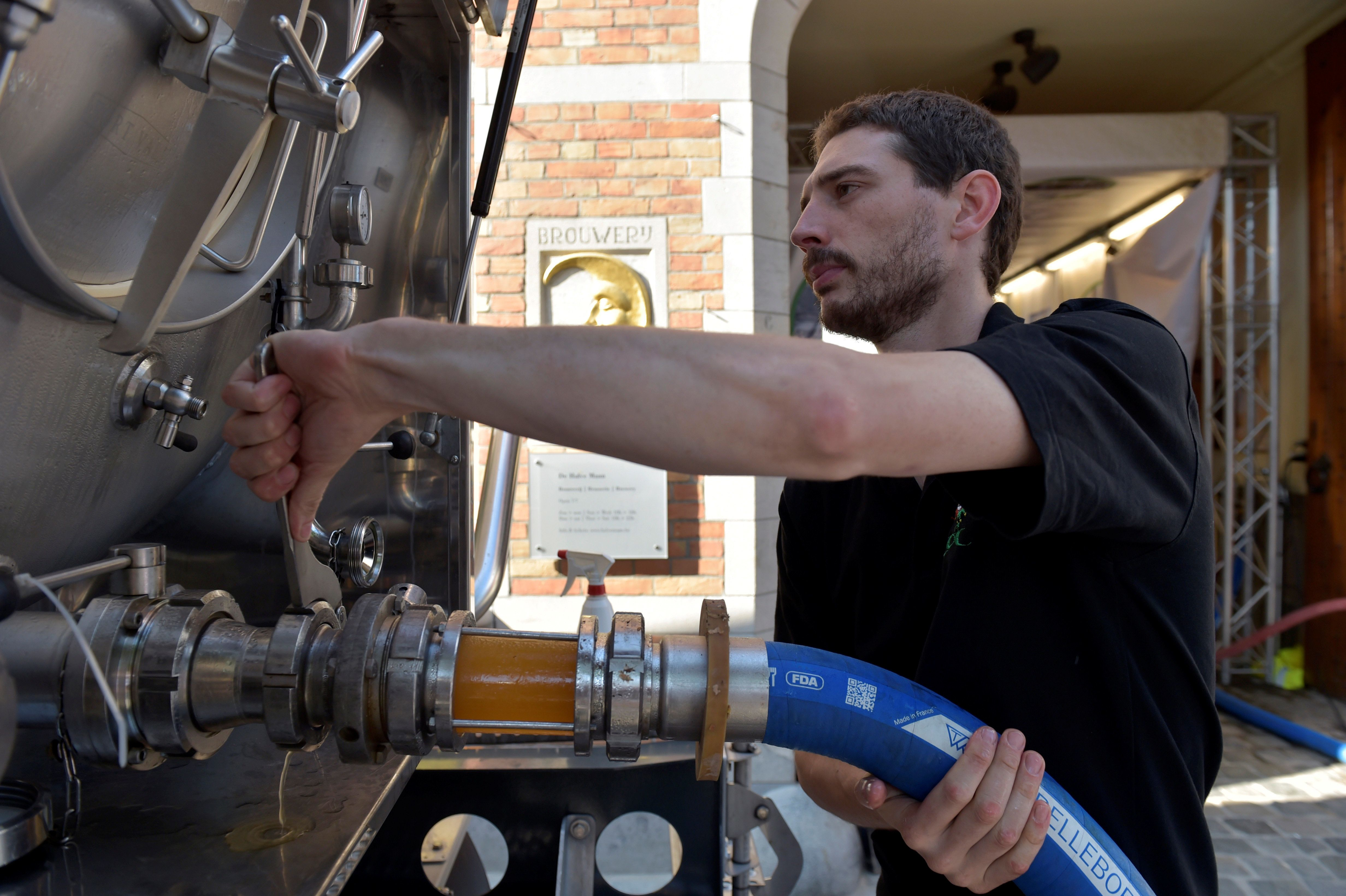 An employee of De Halve Maan brewery connects a pipe to feed beer into a truck  in Bruges, September 15, 2016. REUTERS/Eric Vidal