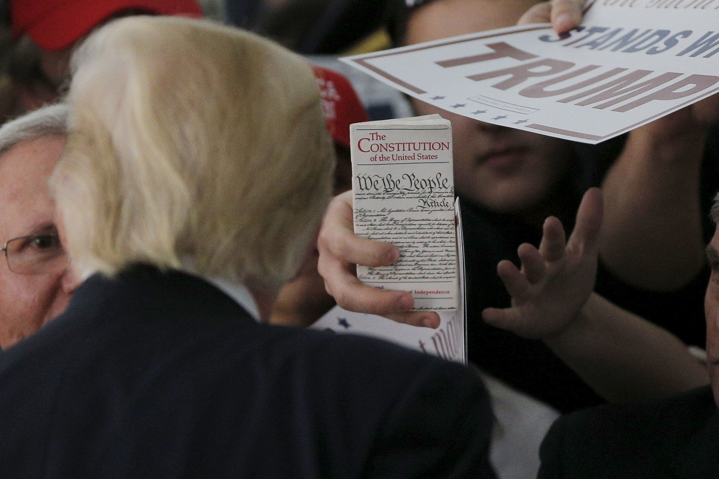 An audience member holds up a copy of the U.S. Constitution for U.S. Republican presidential candidate Donald Trump at a campaign rally in Warwick, Rhode Island April 25, 2016.  REUTERS/Brian Snyder