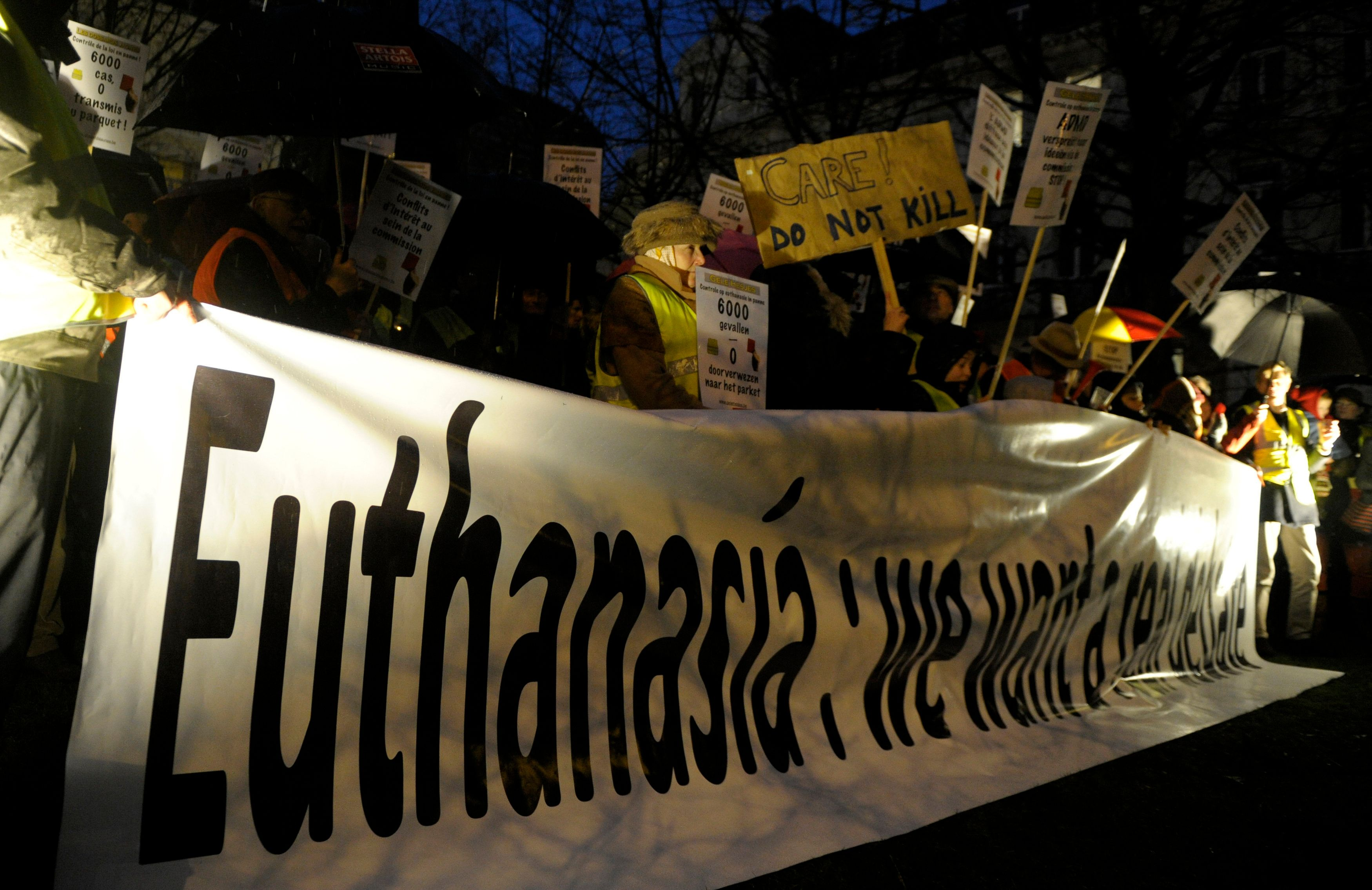 """Protesters, who call themselves the """"yellow jackets"""", hold banners and placards as they demonstrate against a new law authorizing euthanasia for children, in Brussels February 11, 2014. Belgium is expected to pass a new law on Thursday, introducing the right to grant euthanasia for terminally ill children, making Belgium the first country in the world to remove the age limit for the procedure. The new law is going to the Belgian Parliament with MP's expected to pass it after breaking what is an almost universal taboo, when in December last year the country's Senate voted it through a 50-17 majority.  REUTERS/Laurent Dubrule (BELGIUM  - Tags: POLITICS)"""