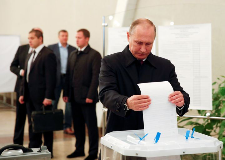 Russian President Vladimir Putin casts his ballot at a polling station during a parliamentary election in Moscow, Russia, Sep