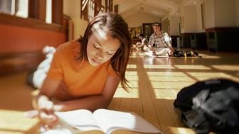 Students studying on floor in corridor