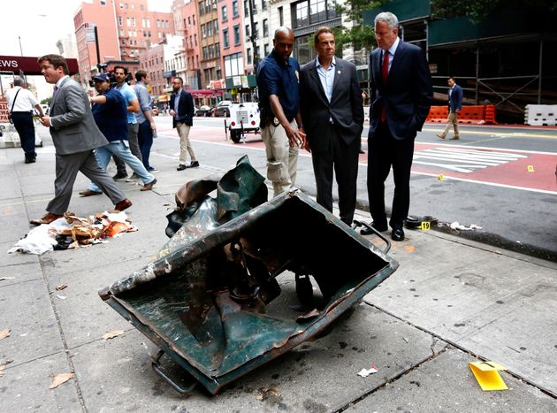 New York Mayor Bill de Blasio (R) and New York Governor Andrew Cuomo (2-R) look over a mangled dumpsterat...