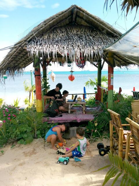 Paul and Caroline King work on laptops by beach in Koh Samui, Thailand while Winston and Henry play with toys on the sand.