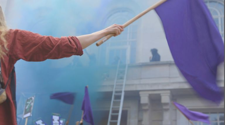 One Sisters Uncut protester waves a purple flag as activists climb onto Hackney Town Hall