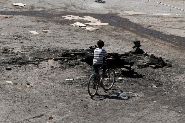 A boy rides a bicycle near a hole in the ground after an airstrike on Sunday in the rebel-held town of...