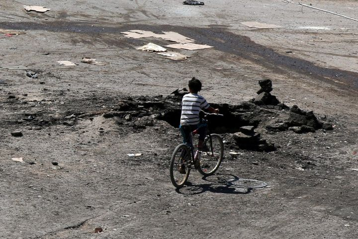 A boy rides a bicycle near a hole in the ground after an airstrike on Sunday in the rebel-held town of Dael, in Deraa Governo