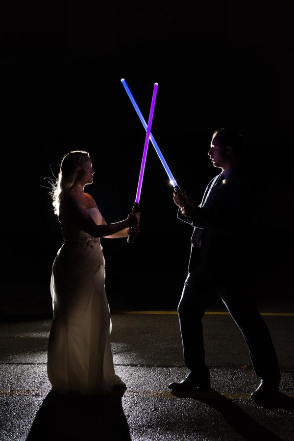 """""""Kelly and Chris ended their perfect wedding day in the best way possible -- with a nighttime light saber battle!"""" — <i"""