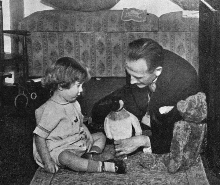 A. A. Milne and his son Christopher Robin Milne playing with a toy penguin.
