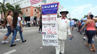 MIAMI, UNITED STATES - MARCH 13:  Santiago Portal, who migrated from Cuba 50 years ago, displays a sign supporting US Presidential candidate Donald Trump on 8th Street in the Little Havana community during the Calle Ocho Festival on March 13, 2016 in Miami, Florida.  (Photo by Sean Drakes/LatinContent/Getty Images)