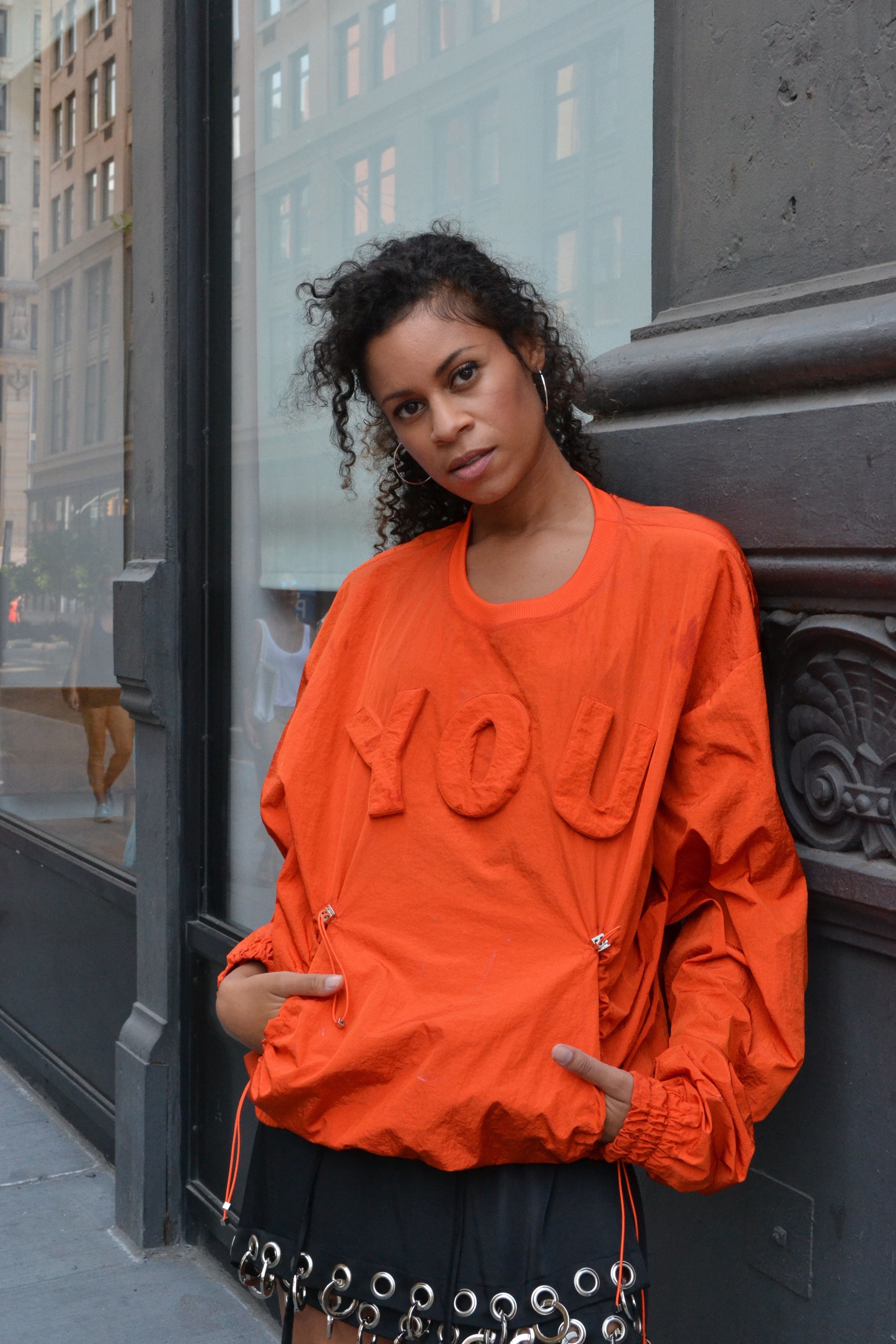 Aluna Francis rocks a bright orange windbreaker while posing along the streets of New York City
