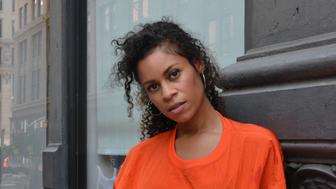 Aluna Francis rocks a bright orange windbreaker while posing along the streets of New York City