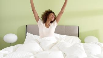 Young woman waking up stretching in bed