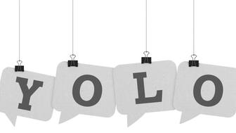 A  3D representation of individual speech bubbles hanging on a plain white background spelling out a word. The speech bubble is hanging from a binder paper clip that is attached to a piece of string. The bubble has a white paper texture. The background is pure white. written out in single letters on the speech bubble in dark grey text is the word Yolo