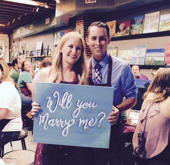 """The happy couple posing with the """"Will you marry me?"""" painting."""