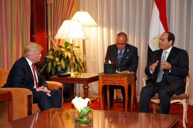 Donald Trump (L) looks on as Egyptian President Abdel Fattah el-Sisi speaks during a meeting at the Plaza...