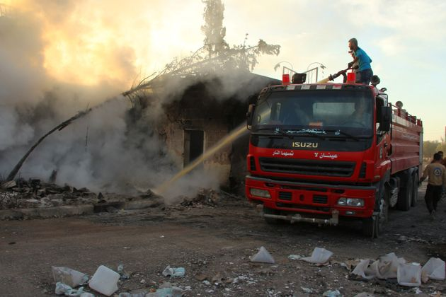 A Civil Defence member and a man put out a fire after an airstrike on the rebel held Urm al-Kubra town,...