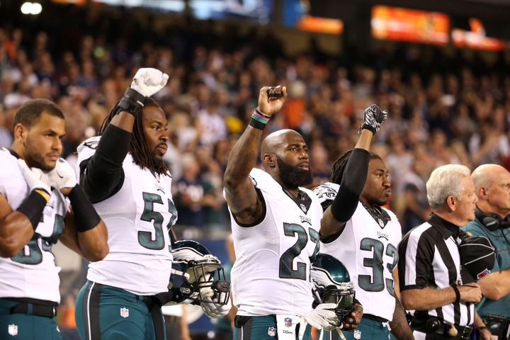 Philadelphia Eagles players Steven Means (51), Malcolm Jenkins (27) and Ron Brooks (33) raise their fists during the national