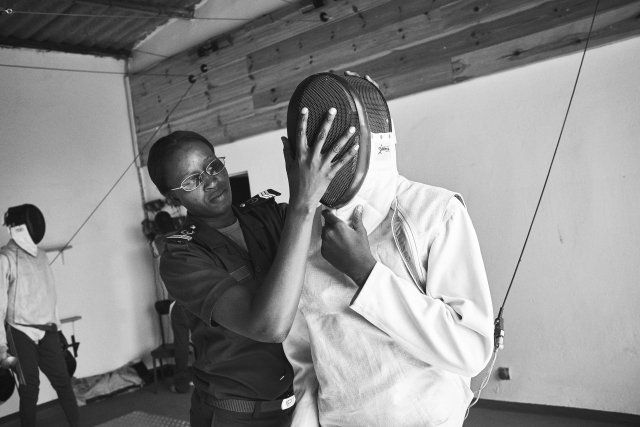 Prison guard Fatoumata Sy assists a boy with his mask, part of a group of minors incarcerated at a nearby prison participatin