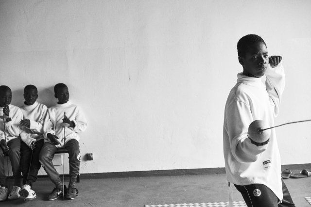 Minors incarcerated at a nearby prison participate in a match during a fencing session at a studio.