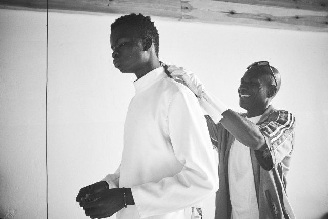 Daouda, 17, dresses in preparation for a fencing match.