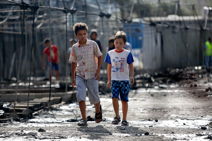 Children walk past the charred remains of tents on Sept. 20, 2016, after a fire ripped through Moria camp.