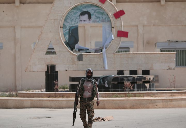 A YPG fighter in Kurd-controlled Hasaka, Syria, with a defaced picture of Syrian dictator Bashar Assad in the background. Tho