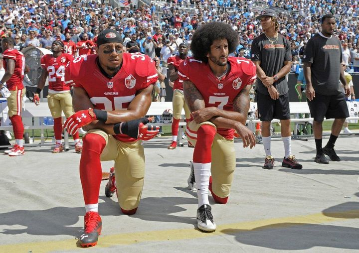 Eric Reid (left) and Colin Kaepernick (right) take a knee during The National Anthem.