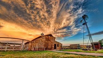 An farmstead barn and windmill at sunset.