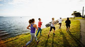 Group of women running together on grass near shoreline at sunset rear view