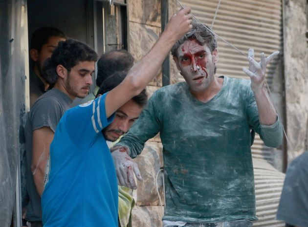 A wounded man is seen after airstrikes near Aleppo, Syria on
